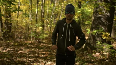 silvicultura : Young Caucasian Handsome Men in His 30s Jogging in a Forest During Fall Season.
