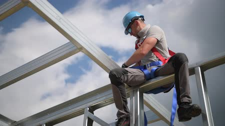 harness : Safety Harness Equipment. Caucasian Contractor in His 30s on a Steel Building Frame. Shock Absorbing Lanyard
