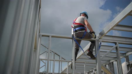 vállalkozó : Shock Absorbing Lanyard and Safety Harness Equipment. Work at Height Safety. Caucasian Contractor on a Steel Building Frame.
