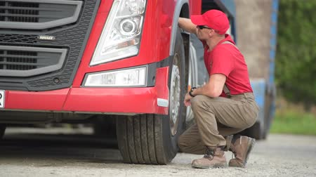 czek : Caucasian Truck Driver Making Quick Tires Check. Transportation Industry.