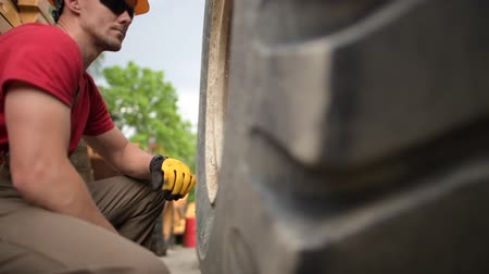 kask : Checking on Bulldozer Wheels. Industrial Theme. Heavy Equipment Mechanic