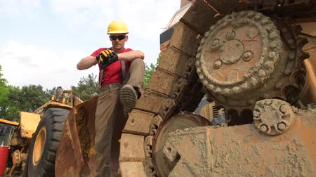 buldozer : Caucasian Heavy Equipment Operator in His 30s Staying Between Machinery. Construction Industry.