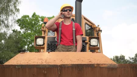 devoir : Caucasian Heavy Equipment Operator Staying on Bulldozer and Talking on a Phone. Vidéos Libres De Droits