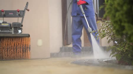 lavagem : Cobble Driveway Pressure Washing by Caucasian Worker.
