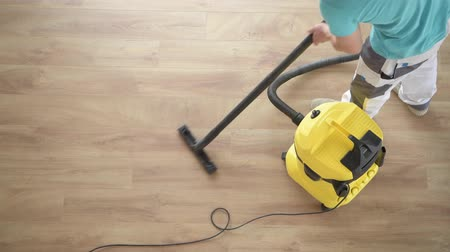 vácuo : Caucasian Men Vacuuming Apartment New Hardwood Floor. Home Cleaning Time.