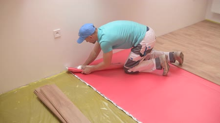 laminát : loor Panel Installing by Professional Flooring Caucasian Installer in His 30s.