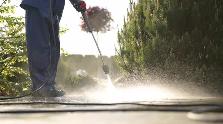 lavagem : Cleaning Brick Pavement in a Garden Using Power Washer.