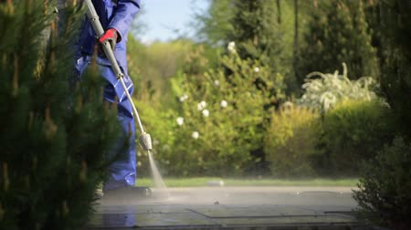 godo : Caucasian Men and the Spring Maintenance. .Cobble Driveway Pressure Washing by Caucasian Worker.