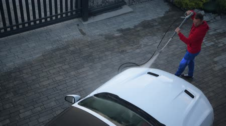 cabriolet : Caucasian Men in His 30s Washing His White Cabrio Vehicle Using Pressure Washer.