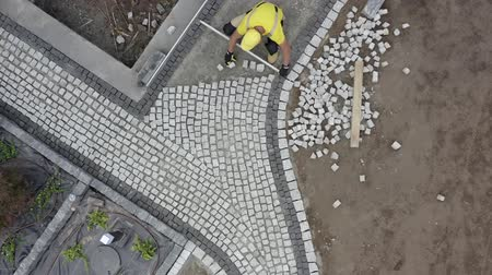 příjezdová cesta : Residential Granite Brick Paving by Caucasian Construction Industry Worker. Aerial Footage.
