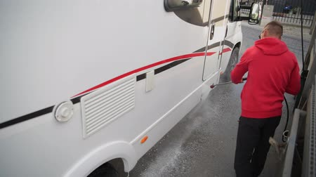 lavagem : Caucasian Men in His 30s Cleaning Outside His RV Camper Van Using Pressure Washer.