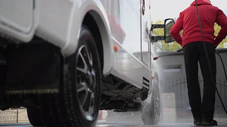 rving : Seasonal RV Recreational Vehicle Motorhome Cleaning Using Pressure Washer. RV Camper Car Washing by Caucasian Men in His 30s.