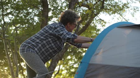 tense : Summer Vacation in a Tent. Retired Caucasian Woman in Her 60s Preparing Her Tent Checking Material Tension.