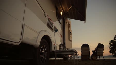 rving : Motorhome Camping Vacation. Woman Relaxing in Front of Her Camper Van Motorhome. Stock Footage