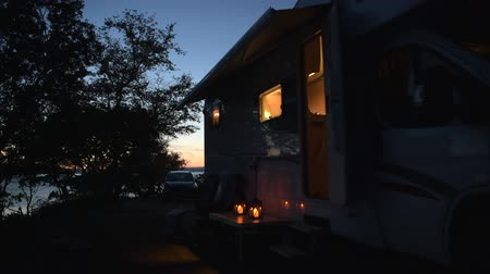 rving : Evening in the RV Park Camping. Modern Motorhome Camper Van and Two Chairs in Front.