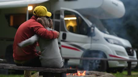 rving : RV Campsite Family Time. Father Hugging His Daughter on Wooden Bench in Front of Campfire and Motorhome. Stock Footage