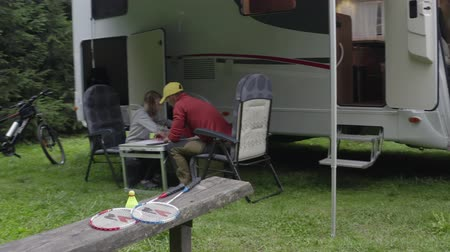 rving : Caucasian Family at the Table in Front of Motorhome RV Camper. Summer Time Recreation. Stock Footage