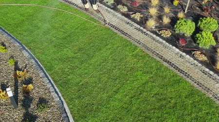 installer : Watering Newly Installed Natural Grass Turfs in a Garden. Professional Gardener with Garden Hose. Aerial Footage.
