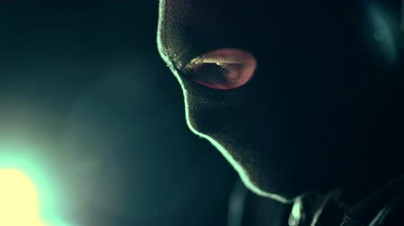 felon : Profile Show of Men Wearing Black Mask Covering His Face. Dark Place with Backlit. Cyber Security Concept.