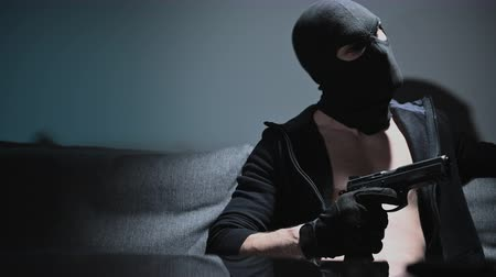 felon : Gang Member Wearing Black Mask with Hand Gun Preparing Body and Mind for the Action.