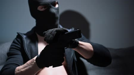 felon : Slow Motion Footage of Masked Gang Member in His 30s. Playing with Handgun. Stock Footage