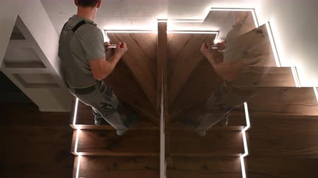 жесткий : Men in His 30s Mopping Wooden Stairs Inside His Apartment. Стоковые видеозаписи