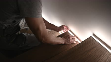 installer : Caucasian Worker Installing LED Wooden Stairs Lighting.