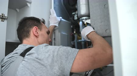 installer : Caucasian Worker Looking Inside Central Gas Heater Trying to Fix the Problem.