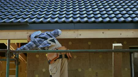 dach : Caucasian Contractor in His 30s on a Scaffolding. Ceramic Tiles House Roof Construction. Wideo