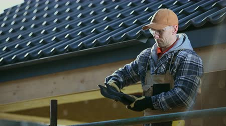 dach : Caucasian Roofing Worker in His 30s with Ceramic Roof Tiles in Hands Preparing For Work. Wideo