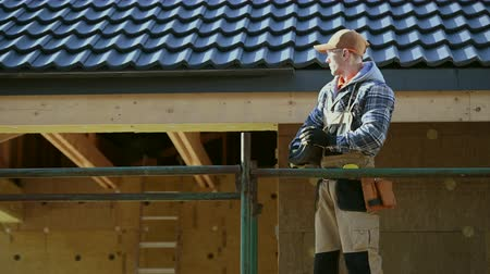 emek : Construction Worker in His 30s with Ceramic Roof Tiles in Hands. Roofing Industry Profession. Industrial Theme.