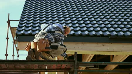 dach : House Construction Theme. Caucasian Contractor in His 30s Working on a Scaffolding. Wideo