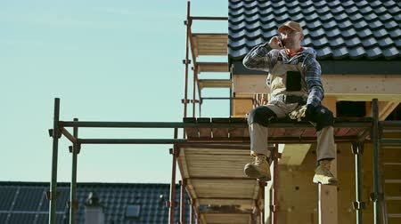 emek : House Construction Worker Making Phone Call While Seating on a Scaffolding. Industrial Business Theme. Stok Video