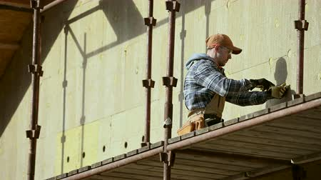 madeira compensada : Mineral Wool Blocks on House Wall. Exterior Walls Insulating Process. Construction Worker.