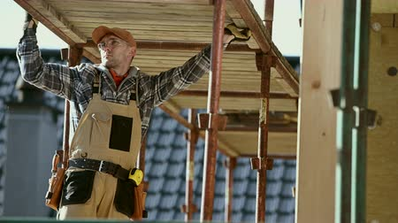 installer : Contractor Worker in His 30s and Scaffolding Assembly. Industrial Theme. Stock Footage