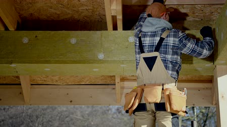 Construction Contractor Worker Attaching Blocks of Insulation Mineral Wool.