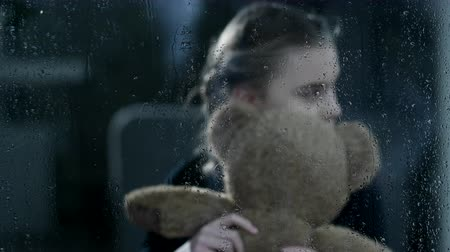 приехать : A Lonely Girl Hugs Her Teddy Bear Tight As She Sits By Herself In An Empty Room. She Looks Anxiously For Somebody Familiar To Come.