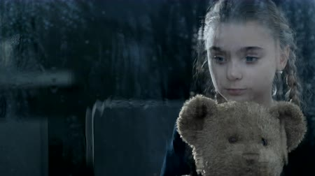 Worried Girl Cuddles Closely With Her Teddy Bear. The Storm Makes The Waiting Room Look Dark And Gray.
