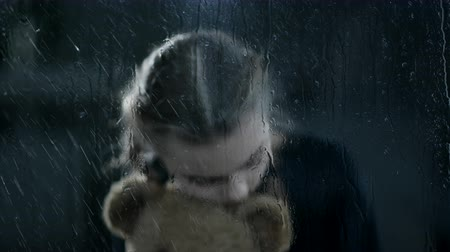 zabawka : School Girl Holds Tight To Her Toy Bear. The Room Is Dark And The Rain Is Pouring Outside. Wideo
