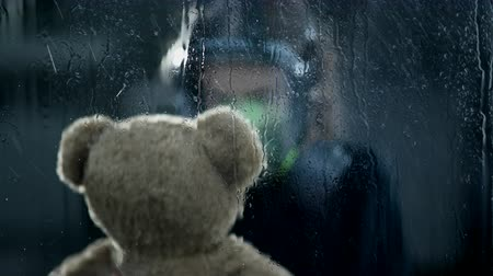 Worried Child Wears Gas Mask While Holding Teddy Bear Tight. It Is Dark And The Rain Is Pouring Out The Window.