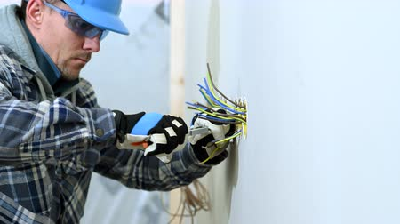 arame : Construction Worker Using Wire Stripper To Get Wires Ready For Plug Installation.
