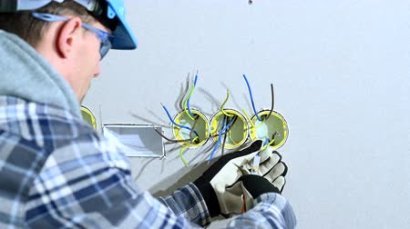 arame : Construction Worker Sorts Out And Arranges Wires In Electric Outlet. Stock Footage