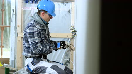 reparatie : Construction Worker Trims Organizes And Groups Electric Wires In Outlet For Future Installation.