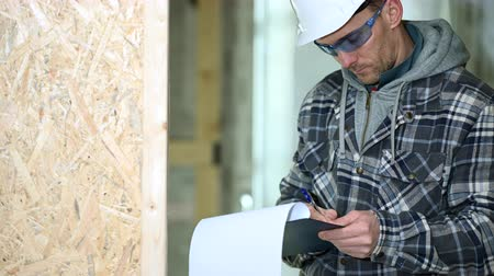 подпись : Male Construction Inspector Makes Notes Of Faulty And Improper Installations On Job Site.