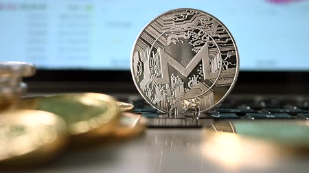 waluta : Pan Up Shot Of Cryptocurrency Represented As Silver Coin With Stock Market Website On Computer Behind.