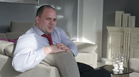 гангстер : businessman sitting in living room on couch and is flirting at the camera