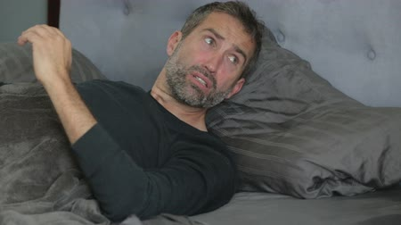 aggódó : man lying in bed and waking up with a headache Stock mozgókép