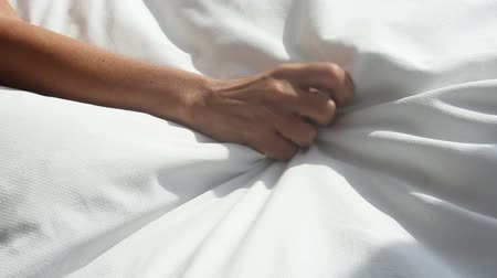 cover : arm of woman grabbing a white blanket in bed and relaxes