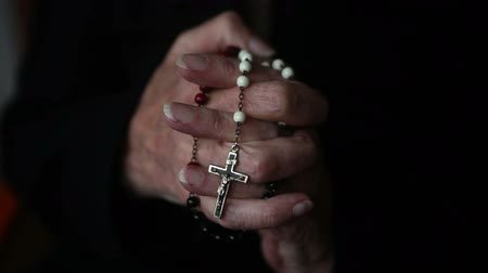 dua eden : closeup of old woman hands praying and holding a rosary