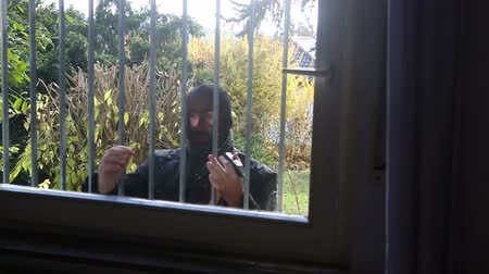 rabló : burglar with mask trying to get into a window Which has iron bars Stock mozgókép